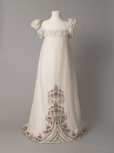 Girl's dress with high waist and puffed sleeves, white muslin embroidered from the hem with a floral design in coloured wool, made in England, 1812-1815.Girl's dress of white muslin embroidered from the hem with a floral design in coloured wools. The dress has a high-waisted bodice, vertically-gathered puffed sleeves and a trained skirt.Muslin embroidered in wool.
