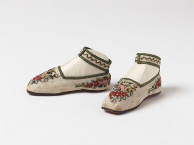 Pair of shoes for a girl, white canvas embroidered with dahlias and roses in coloured wool and bound with green ribbon, made in England, 1851.Pair of shoes for a girl, white canvas embroidered with dahlias and roses in coloured wool and bound with green ribbon.Canvas, embroidered in wool and bound with ribbon.