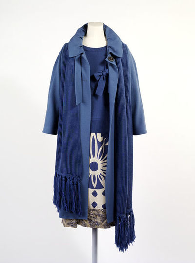Blue wool and silk ensemble with leather shoes, Betty Jackson, 2005, Britain.Blue wool jumper with three-quarter length sleeves and a ribbed collar, cuffs and hem, featuring a bow across the bodice. Chunky blue wool knit scarf with a long fringe at the ends. Blue wool coat with ruched collar, three-quarter length sleeves, a bow at the neck and two hip pockets. Lined with the same-coloured blue silk it has a two-button closure at the neck. Cream and blue printed silk skirt with a floral pattern and featuring silver and gold sequins at the hem. Metallic leather slingback with square toe and bow. Metallic leather slingback with square toe and bow.Knitted wool; Wool; Silk; Metallic leather.