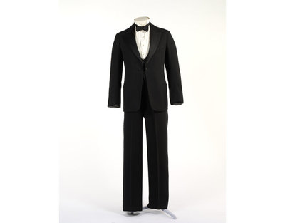 Woollen three-piece dinner suit, made in Great Britain, 1928-1929.Black dinner suit consisting of a jacket, trousers and waistcoat of black wool. The inside of the jacket is lined with black silk, and the sleeves with striped cotton. The waistcoat and trousers are lined with the same cotton as the jacket.Wool and cotton.