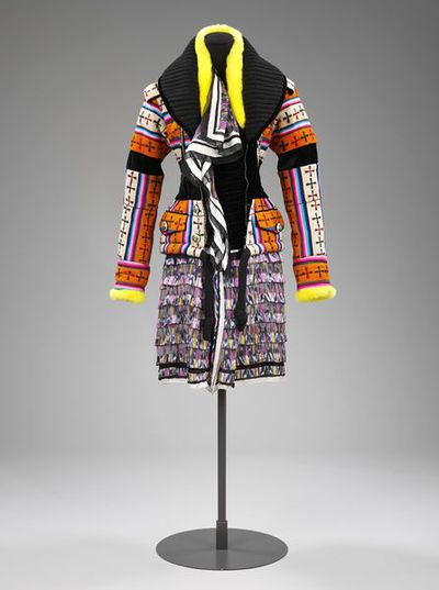 Ensemble.Woman's two-piece ensemble; jacket with padded shoulders creating a wide, square shoulder line, long sleeves and a fitted waist with a short peplum, vibrantly multi-coloured stripes with wide bands of black velvet round upper arms and waist, predominant colours are orange and pink; dress, mini length, made from silk printed in a multi-coloured ikat-style design in mingled shades of shocking pink, yellow, blue, white and black.Printed silk .