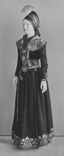 Bridal costume of wool, velvet, gold braid decoration and metalwork.The costume consists of the following elements, as described by Elsa E. Guðjónsson in 1985: Pelisse (Hempa) of black cloth, bordered with velvet and fastened in front with silver gilt clasps. Two circular silver gilt disks on the breast, with cord and pendent ornaments and the monogram 'S. N. D.' in white paste. Bodice (Upphlutur) of green velvet, with five silver gilt clasps, attached to a petticoat (Fat) of green cloth. Petticoat (Fat) of dark blue cloth, with flowers in coloured worsted tamboured around the skirt. Jacket (Treja) of black velvet with gold embroidery and silver-gilt buttons of globular openwork; collar (Kraga) of black velvet and gold embroidery. Apron (Svynta) of dark blue cloth tamboured with flowers in coloured worsted, fastened with silver gilt openwork bosses. Silver gilt neck chain (Hals festi) of open work scroll links, from which is hung a medallion (Nisti). The medallion is silver gilt cordate with a blue stone in its centre, around which are engraved the initials 'H.H.D. 1782'. Silver gilt shoulder chain (Herðafesti) composed of seven circular disks of cord ornament connected by triple chains, and joined to a transverse bar, on the centre of which stands a vase-shaped ornament, and from which is hung a cross with foliated ends decorated with a figure of the Trinity & the Evangelistic symbols. To the central disk is likewise suspended a medallion (by Heinrich Ritz?) showing on the one side the Crucifixion, on the other the sacrifice of Isaac. Girdle (Lyndi) of green velvet, with oblong silver- gilt plates of openwork corded ornament (32 in all, two missing,) with a pendant of similar character. ;Head-dress, faldur, spaðafaldur, of plain woven cotton or linen base, with plain woven silk covered the stiffened curved form, like a hook, pins all along edge of curve.;Sleeveless bodice, upphlutur, of light green velvet decorated with gilt braid and fastened in front with five (o