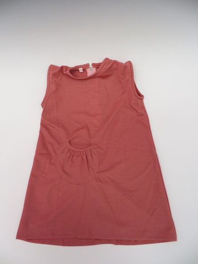 Girl's shift dress, dusky pink nylon fabric a-line style, sleeveless with a high neck and one decorative pocket on the front, size 22 months, probably made in England, 1970s. A-line dress made of a synthetic dusky pink coloured fabric. The fabric has a sparkly quality and it is stretchable. It is sleeveless and has a high round neckline. It fastens at the back with a metal zip which finishes in the middle of the back.  The dress is constructed in three main pieces, one front panel and two to form the back, dissected by the zip. The front of the dress has an applied decorative flat pocket, circular in shape, with a scooped opening at the top. The dress has a size label inside at the neckline, '22' that suggests the dress is for a girl of just under 2 years old.  The dress seems cheaply made and the finish and the seams are basically executed.Machine stitched, 100% acrylic material.