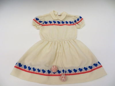 Girl's dress of cream synthetic and wool mix, made for John Walsh, Belgium, 1958-1960. Cream dress with short, puffed sleeves, knitted cuffs and waistband. The dress has a high neck and Peter Pan-style collar. The waistband is gathered using a threaded drawstring belt made of  strands of wool and two pom poms at the ends. The dress is plain cream fabric of a wide woven fabric. It has been embroidered in wools with the repeating motif of a blue duckling and an intermittent line of red running stitches. The pattern is repeated around the chest and sleeves of the dress and all around the hem. The dress is unlined and has a wide and hand-tacked hem. The dress fastens at the back using three buttons, opening to the waist.Machine stitched.