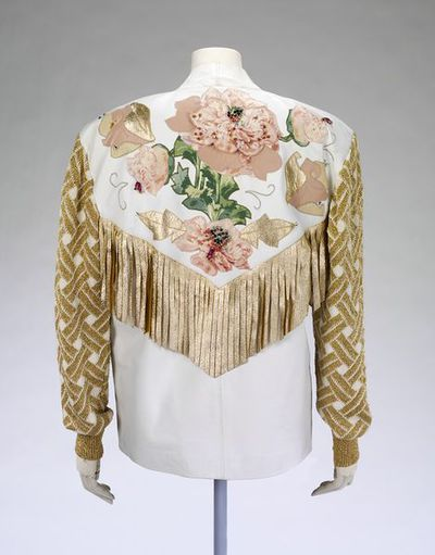 Jacket, F, white leather with knitted gold sleeves, appliqué and fringe, Beth Brett, Britain, ca. 1985.