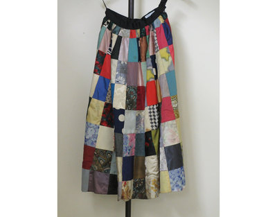 Patchwork skirt, made by Naomi Salmon, probably made in London, ca. 1955.Full skirt entirely made up from multi-coloured blocks, mostly of dress silks, but including cottons, woollens, satins and green Lurex. Each length of patches gradually get wider towards the bottom.  Lined and mounted on a rich sea-green iridescent taffeta with the same fabric flounce around the inside of the hemline. Some discolouration to the lining, particularly where black patches are on the outside.Patchwork of dress silks, satin, cotton, wool and lurex lined with taffeta.
