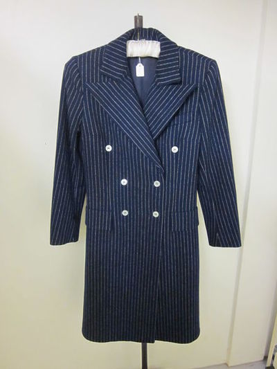 Woman's double-breasted coat in wool, Jaeger, Great Britain, 1970s.Woman's fitted coat in navy wool with broken pinstripe in white. Double breasted with white buttons. Lined in navy Tricel (a triacetate lining fabric). Faux pocket flaps on the hips. Knee length.Wool lined with synthetic fabric.