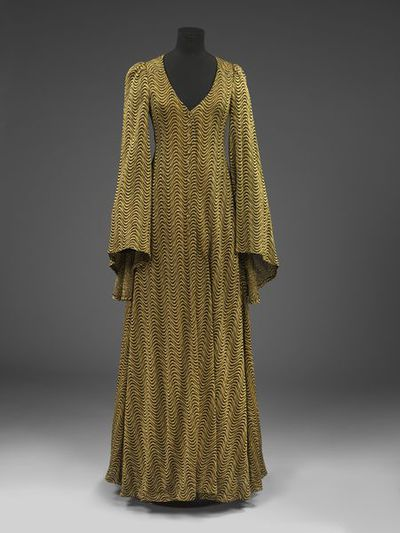 Woman's evening coat and turban hat in knitted rayon and lurex, designed by Biba, retailed in London, ca. 1970. Woman's evening coat and matching turban hat in gold and black rayon and lurex knit. Coat with a front and back yoke, cut in one, and self lined, with double top stitching. It has a centre back seam, and the front and back are flared out from the yoke. Collarless and fastens with 14 small buttons, the interfacing is of acetate lining. The sleeve, which is gathered into the shoulder, is long and very flared. It has a wrap round belt which runs across the inside back and out through the side seams. Hat pleated at the front and back.Knitted rayon and Lurex.
