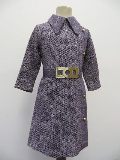 Woollen girl's dress in a purple and cream zig-zag pattern, with a belt with gold plastic buckle, 1970s.Girl's dress made from purple and cream woollen fabric in a zig-zag design. The dress comes with a belt made from the same material and features a plastic gold buckle at the front. This buckle is decorative as the belt does up using a series of poppers located at the back of the belt. The dress has a single pleat down the left hand side, from shoulder to hem, featuring a different, spotted pattern but using the same colours. This pleat has four decorative gold buttons sewn onto it, but unlike the buckle, these are made of metal. The collared dress does up using a metal zip, and a hook and eye, located at the back. It also has a lining made of cream, synthetic fabric.
