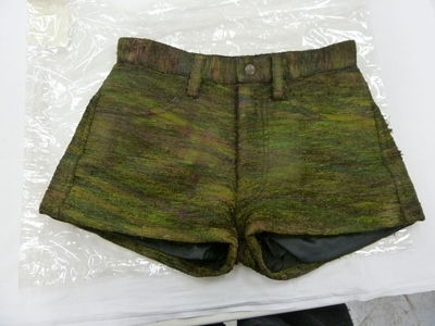 Shorts made of peacock feathers woven with silk and lined with nylon, designed by Maurizio Galante, Italy, late 1997.Pair of shorts made from silk and woven peacock feathers creating an iridescent/burnished green-brown effect and unusual texture. Zipped pockets in the back. Lined in 100% polyamide black nylon with a rubbery reverse texture.Peacock feathers woven with silk and lined with nylon.