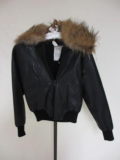 Leather blouson jacket with lining, designed and made by Valentino, Italy, 1973.Black leather blouson jacket with ribbed wool cuffs and waistband, and a chunky plastic zipper down the front. Lined in ribbed black fabric. Button-in lining of black wool with murmaski fur collar.Leather, wool, plastic and fur.