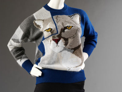 Knitted jumper with animal motif, Krizia, ca. 1985, Italy.Long-sleeved, round-necked knitted jumper in blue cashmere, wool and angora mix, with grey wool patterning on the sleeves and an image of a large cat's head motif on the front in shades of grey, cream and brown.Knitted, in cashmere, wool and angora mix.