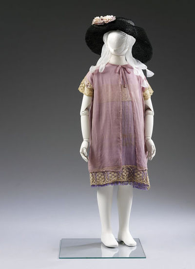 Bridesmaid's; Mauve satinised cotton, English, 1925. Bridesmaid's; Black crin, English, 1924.Round-necked dress, on a foundation of pale mauve satinised cotton, with an overlay of mauve rayon net (having panels of gold thread in the weave), veiled with lilac crepe, and edged with a broad band of embroidered net matching that on the chest of the dress. The garment has a built-in coat of lilac crepe with a self bow at the neck front, and short sleeves of embroidered net. The garment is trimmed with running stitch in pale blue silk round the edges of the crepe roses at the left hip. The fastening consists of press studs on the left shoulder. Soft, broad-brimmed hat of black crin with a deep crown partly nicked. The hat has been made by stitching a single length of crin spiralwise into the required shape.