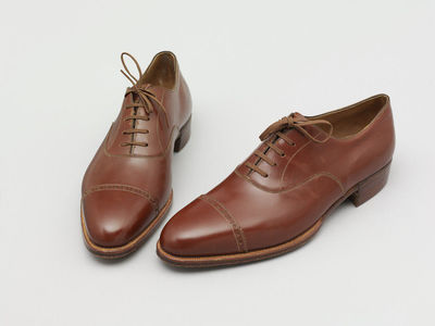 Pair of men's shoes with lace-ups and two wooden shoe trees, made by Moykopf, England, 1933.