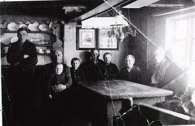 Grøndalen,86.45, ca. 1927. Mekkel Grøndalen har skrive bak på fotografiet: Interiør hjemme. Far sitter med John foran skapet. John Halbjørhus sitter i høgsetet med Olaf, og så har Halvor og Svein på siden. Den nye gårdsbestyreren, Knut Halbjørhus, står foran skapet.