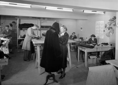 PER BAKKE A/S PELSFORRETNING, TORGGT. 36. HAMAR, INTERIØR, 1950. Her justerer Pauline Evensen en pelskåpe.