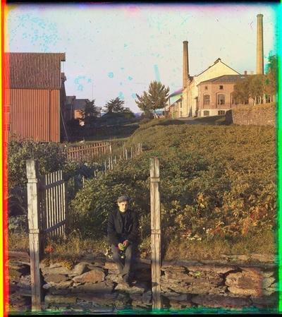 Ung mann sittende ved Levangersundet, med brygge, melkefabrikken og kirkegårdsmuren i bakgrunnen.