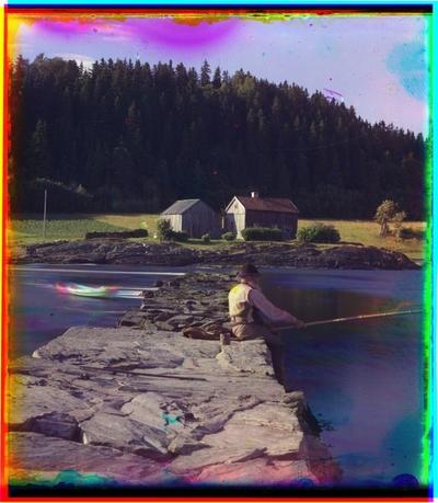 En mann sitter og fisker på Jeteen med husmannsplassen Nesset i bakgrunnen.