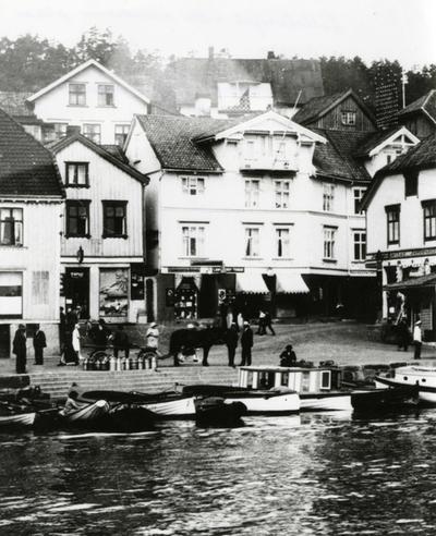 Lilletorget , nå Lauersens plass, ca. 1930. Hestetransport med melkedanker til meieriet. Båten med de store vinduene som ligger på 'asbjørnsens brygge bkle kalt Blomstebåten. Den var dampdrevet og kom lydløst i forhold til andre båter som smelte med eksosen.