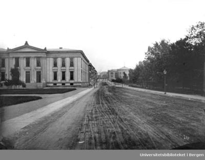 Bygningen til venstre er Norges første universitet, Universitetet i Oslo, Karl Johans gt. 47. Bygningen er oppført av arkitekt Christian H. Grosch etter tegninger av Arkitekt Karl Friedrich Schinkel. Universitetet ble tatt i bruk i årene 1851-54