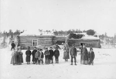 Skoltesamer foran et hus i en russisk skoltelandsby 1890-årene. (Øvreskolteby)
