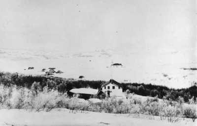 Parti av Kirkenes april 1896. I forgrunnen distriktslegeboligen Solheim og kirken i bakgrunnen. Fjorden frosset en mil utover.