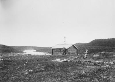 En mann foran St. Georgs greskortodokse kapell i Skoltebyen i Neiden 1904-1905.