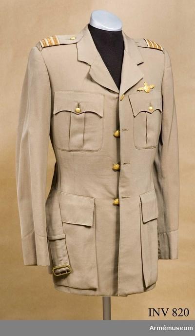 Vapenrock, Vapenrock för kapten vid flygvapnet, Egypten : Stl 50. Tropikuniform av tunt, beigefärgat yllediagonal. Enkelradig med knappar med etiopiska vapnet, utförda i gulmetall. Fyra st. Utan livsöm, med krage och slag. Utsydda bröstfickor med faso- nerade lock och bälgar. Locket fastknäppt med liten knapp. Utsydda sidfickor med raka lock. Sprund i ryggen. Mittsöm bak. Figursydd fram. På ryggstycket två st tränsar sydda av knapphålssilke, för fasthållande av skärpet. Fasonerat, fast ärmuppslag. Fastsydda axelklaffar vid ärmen, fastknäppta vid kragen med liten knapp. Axelhylsor med gradbeteckning, tre guldgaloner=kapten. Fodret är matelasserat över bröstpartiet. Grått konstsiden. Ärmarna fodrade med svart/vit-randig taft. Alla knapphål är tränsade.