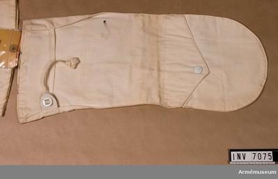 Handske arbm/1943, ArbetsmodellHandske arbm/1943 till snödräkt : Handske t snödräkt arbm/1943. Maskinsydd i vit poplin och försedd med skaft med åtdragsband. Har tumme och är försedd med ett lock på översidan av handen, som täcker ett tvärs över gående sprund. Genom sprundet kan  man få hela handen fri. Locket är försett med en vit  tryckknapp.