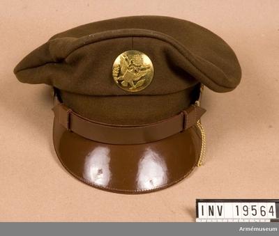 Skärmmössa, Skärmmössa, USA : Skärmmössa för amerikanska infanteriet under andra världskriget. Mössan är i ull och med en skärm av plast. Ett plastband är fastsatt med två metallknappar på skärmen. Ovanför skärmen finns et större märke i metall med en örn hållande en lager och en fackla. Mössan är märkt på insidan med Per Rabe. För Per Rabes levnadsteckning se inventarieförteckning och arkiv.
