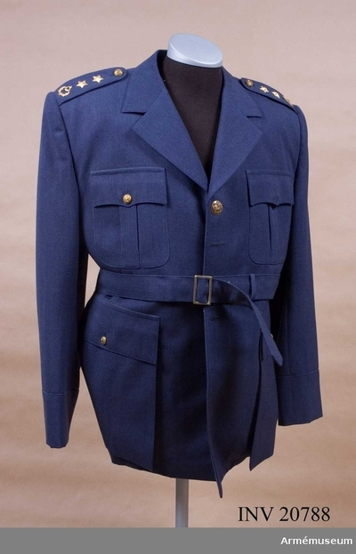 Vapenrock, Vapenrock för överstelöjtnant vid flygvapnet, Turkiet : Grupp C I. Av blågrått kläde. Enradig med 4 knappar och knapphål med 4,5 cm brett tygbälte, som är fastknäppt vid midjan och har spänne. På baksidan sprund, 33 cm långt. Axelklaffar av samma tyg, b:5 cm, l:13 cm. De har en femuddig stjärna och turkiska emblemet av gul metall; krans, måne och stjärna, Fickor 4 st, 2 sido- och 2 bröstfickor som har verti- kala motveck och lock i vinkelform -  sidfickorna med fyrkan- tiga dito. Foder av gråblått bomullstyg. Knappar av gul metall, 2,5 cm i diameter. Kragen liggande öppen. Ärmuppslag rakskurna.
