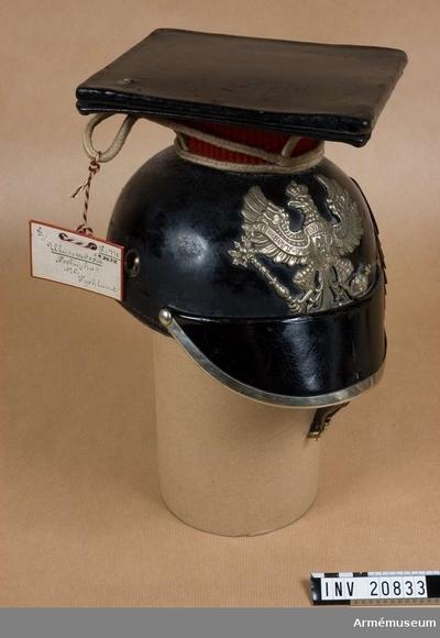 Lansiärmössa m/1867, Lansiärmössa m/1867 för menig, Preussen : Grupp C. Ty. tschapka. Av svartlackerat läder med stor framskärm och beslag av ny- silver. Alla mössans metalldelar är av nysilver, utom hakrem. Foder av svarta läderbitar som fästes med lädersnören som dock saknas här. Hakrem av läder med cislerade fjäll av mässing; endast den V delen med spännen finns kvar. Vapenplåt på mössans framsida med den preussiska örnen med svärd och spira. På örnens bröst finns bokstäverna
