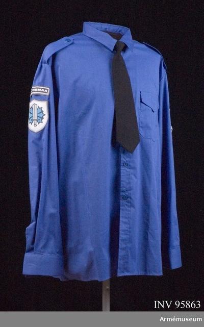 Skjorta, Skjorta för Överkommissarie vid gränsförsvaret, Estland : På höger ärm: Ett tecken med uppåtriktat svärd (försvar), framför blåklint (Estlands nationalblomma). Ovanför detta