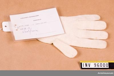 Vante, FemfingervanteModellexemplar : Stickad, vit femfingersvante av ylle. Handen glattstickad och mudden ribbstickad. Av kamgarn.  Vidhängande etikett: