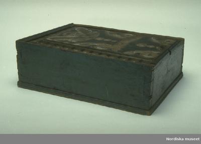 TimplådaInventering Sesam 1997-1998: L 47, B 35, H 15 cm Timplåda, rektangulär, med skjutlock, av barrträ. Utanpåliggande botten fästad underifrån med dymlingar av trä. Sidorna ihopfogade genom sinkning. Profilerade lister skurna upptill i massivträet på tre av sidorna, en list är trasig. Locket har en förhöjd mittspegel med profilerade kanter, utskuret snitt att greppa i vid öppning. Urtag på ena sidan kan ha varit till någon form av låsanordning. Utvändigt målad i blått, lockets spegel med kurbitsdekor i gult, vitt, svart och brunt, på ena kortsidan