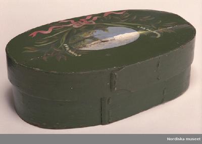 MössaskInventering Sesam 1997-1998: L 36,5, B 22,5, H 11 cm Mössask, oval. Botten, lock och svep av barrträ, utan falsar. Svepen fästade med små spikar av järn. Hopfästning av svepen med rottågor, släta stygn, två rader, övermålade med grön färg. Svepen och lockets ovansida grönmålade. Lockets ovansida med målat landskapsmotiv, runtom liljekonvaljer och gröna blad samt en ljusröd rosett.  Spricka i locket. Till förvaring av stycke och mössa. AMB 1997 Agnetha Blomberg