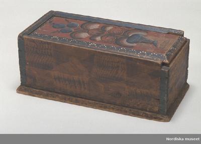 TimplådaInventering Sesam 1997-1998: L 35, B 18, H 14,5 cm Låda, rektangulär, med skjutlock, av barrträ. Utanpåliggande botten, fästad underifrån med dymlingar av trä, fotlist. Sidorna sammanfogade genom sinkning. Skuren profillist i massivträet upptill. Lock med fasade kanter, utskuret snitt att greppa i vid öppning.  Utvändigt målad i brunt, dekormönster, listerna upptill och hörnen målade i blått. På locket kurbitsmålning i blått, vitt och svart mot röd botten, i vitt