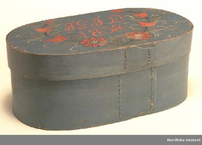 MössaskInventering Sesam 1997-1998: L 55,5, B 32, H 19 cm Spånask, oval. Botten, lock och svep av barrträ, utan falsar. Svepen fästade med dymlingar av trä. Hopfästning av svepen med rottågor, släta stygn, två rader. Svepen och lockets ovansida blåmålade. På lockets ovansida målat i rött