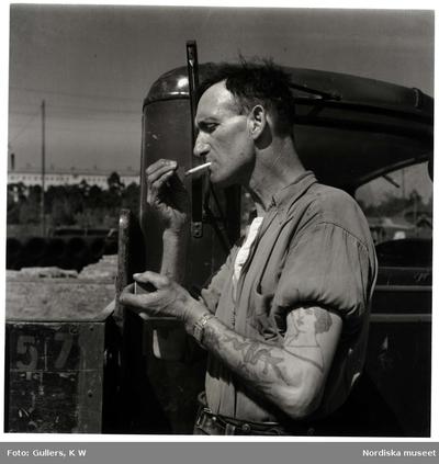 Lastbilschaufför med tatuerade armar tänder cigarett.