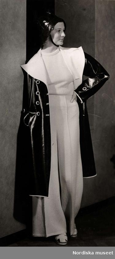 Dammode, en kvinnlig modell som är klädd i en vit tröja och byxor. Samt en svart regnkappa och regnhatt. Nordiska Kompaniet 1938.