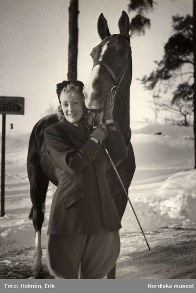 Fru Karin Ekelund från Herrskrädderiet på Nordiska Kompaniet iklädd ridjacka och ridbyxor i snöigt landskap tillsammans med häst.