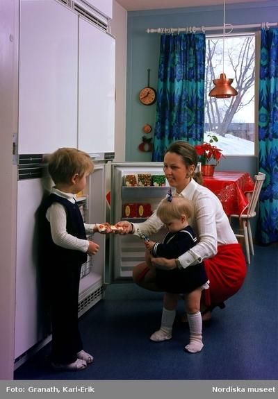 7b420a6755e2 Kök. Kvinna med två barn hämtar glass i frysskåp.