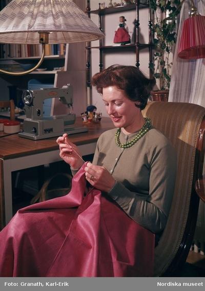 Handarbete. Kvinna sitter i fåtölj och syr för hand. I bakgrunden en symaskin