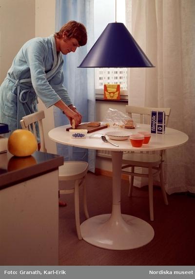 Man i morgonrock dukar frukostbord.