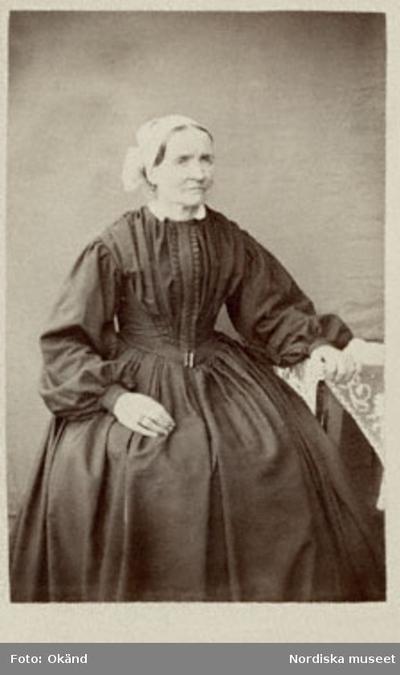 94c96c782d53 En kvinna i en lång mörk klänning, sitter vid ett bord