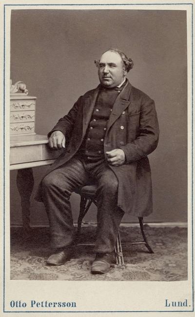 9153b07a5ee4 En man poserar sittande vid ett skrivbord. Från Saxtorp, Harjagers härad i  Skåne.