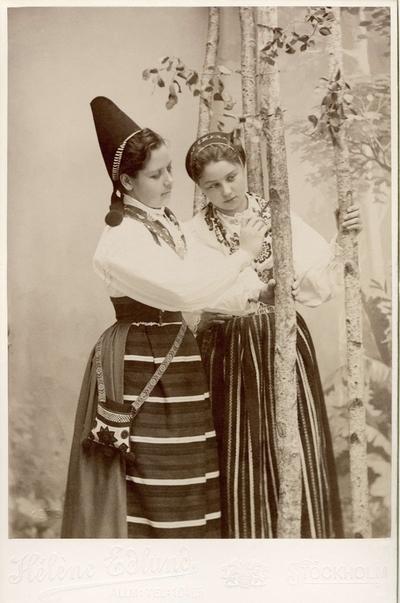 Två unga kvinnor poserar i olika folkdräkter