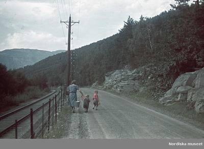 En kvinna i blå klänning går barfota på en grusväg och bär två hinkar med ett ok. Bredvid henne går två små barn