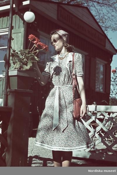 Kvinna i småblommig klänning med bolero som studerar röda blommor i en kruka utanför Källhagens värdshus.