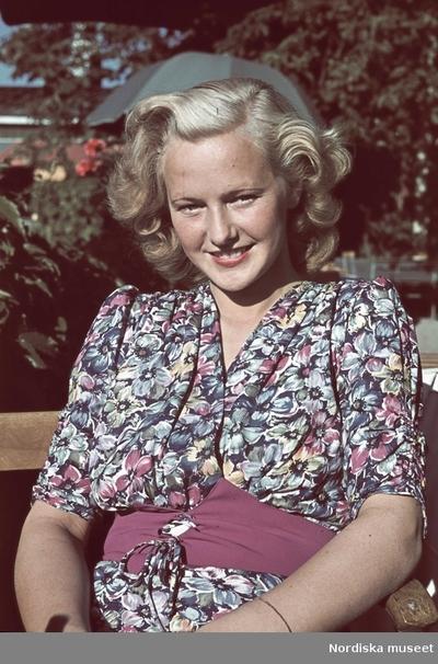 Blond kvinna i blommig klänning.